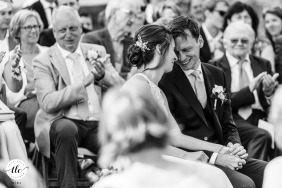 Rye Island, Henfield, West Sussex foto de la boda de la novia y el novio compartiendo un momento amoroso rodeado de sus amigos y familiares