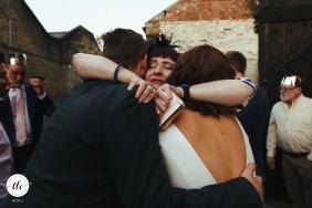 Clapton Country Club, imagen de la recepción de boda en Londres de la pareja abrazada por un amigo de la familia