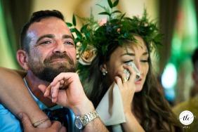 Renaissance Event Center, Kingston Fotografía del momento de la recepción de la boda de Canadá creada cuando la novia y el novio lloran y se toman de la mano mientras escuchan los discursos después de la cena