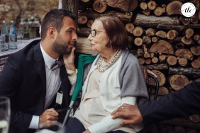 Agriturismo IL RIGO, San Quirico d'Orcia, Siena documentary wedding moment of the aunt of the groom speaking softly to his nephew while a hand comes out with love