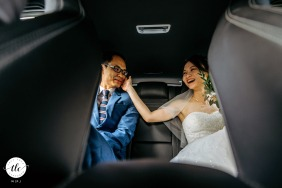 Singapore real moment wedding image of a couple enjoying a brief intimate moment in the car on the way to their wedding banquet