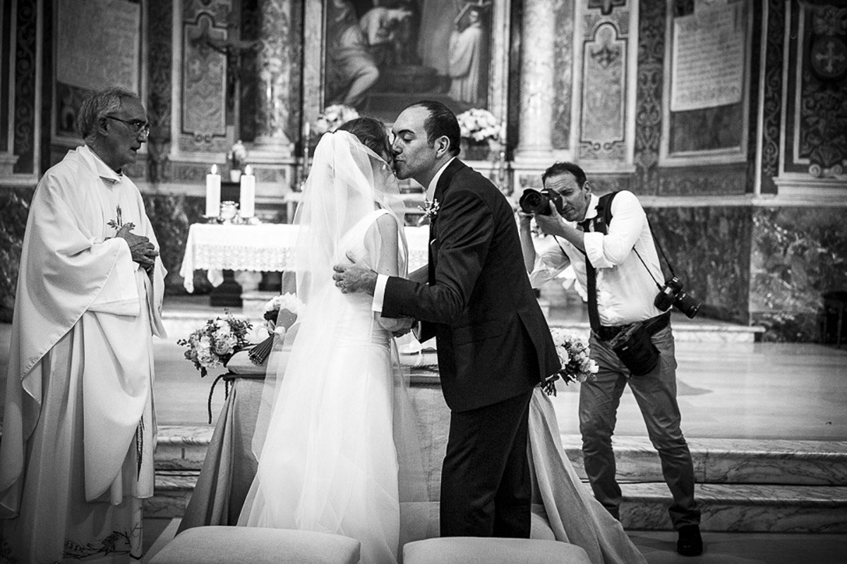 Italy wedding photographer capturing a ceremony kiss in Lazio Rome - Image by Alessandro Iasevoli