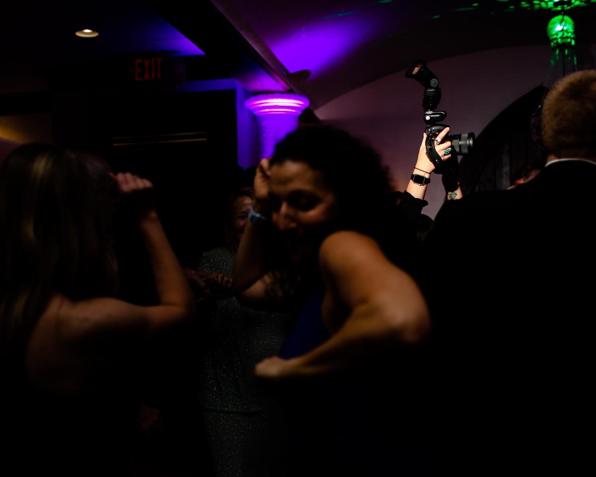 Huwelijksfotograaf die binnen op de dansvloer mengen met camera boven hoofd die foto's nemen
