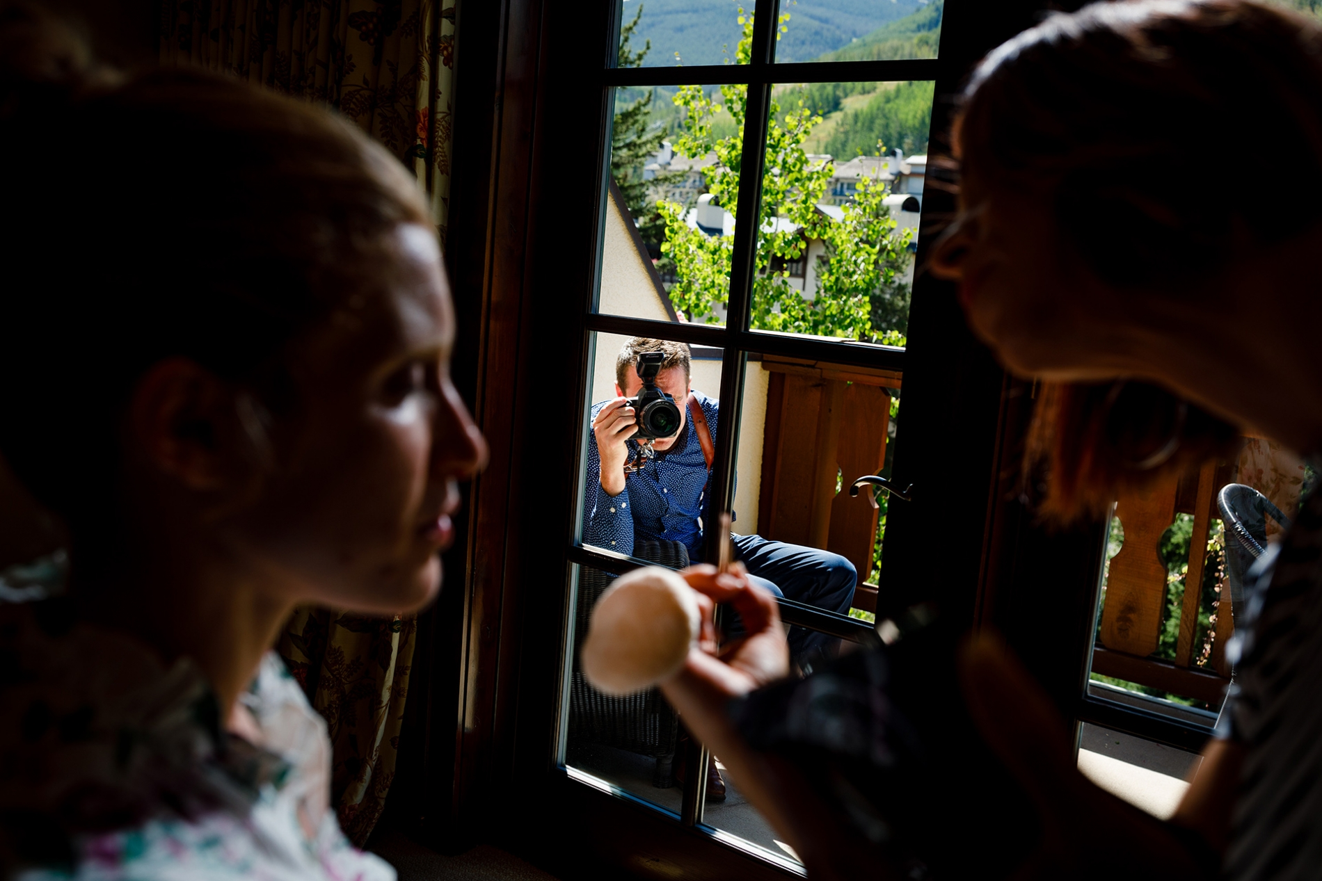 Silverthorne Colorado wedding photographer shooting pictures of the bride through a window.