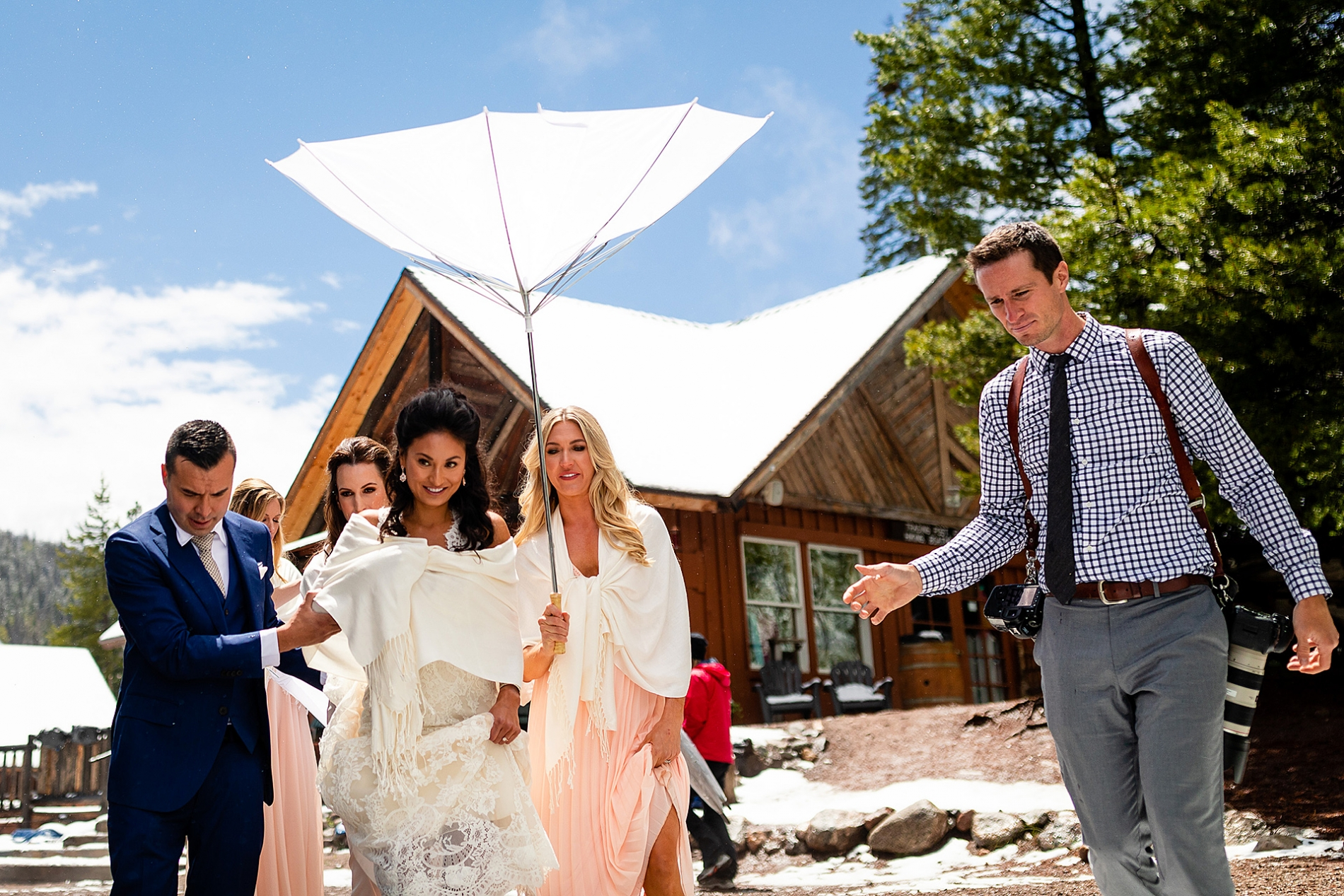 Silverthorne Colorado photographer at wedding walking with the bride under an umbrella.