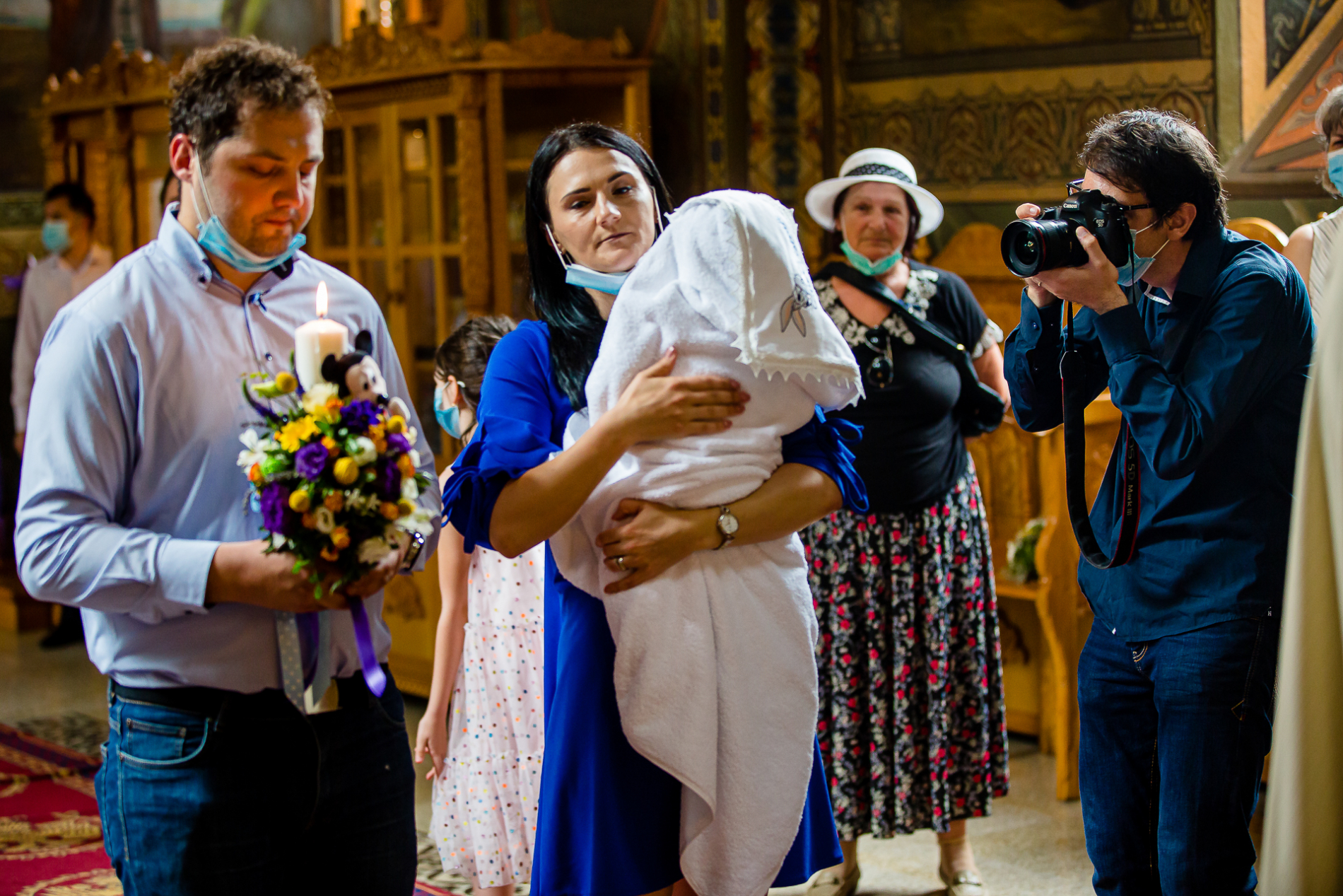 a wedding photographer practices social distancing at a Bucharest Romania ceremony while wearing a CORONAVIRUS mask