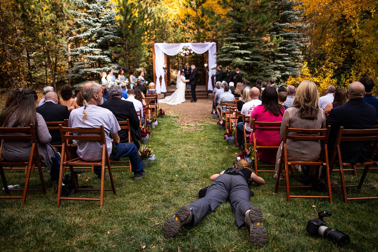 The Colorado photographer lays sprawled out on the grass during the outdoor wedding ceremony.