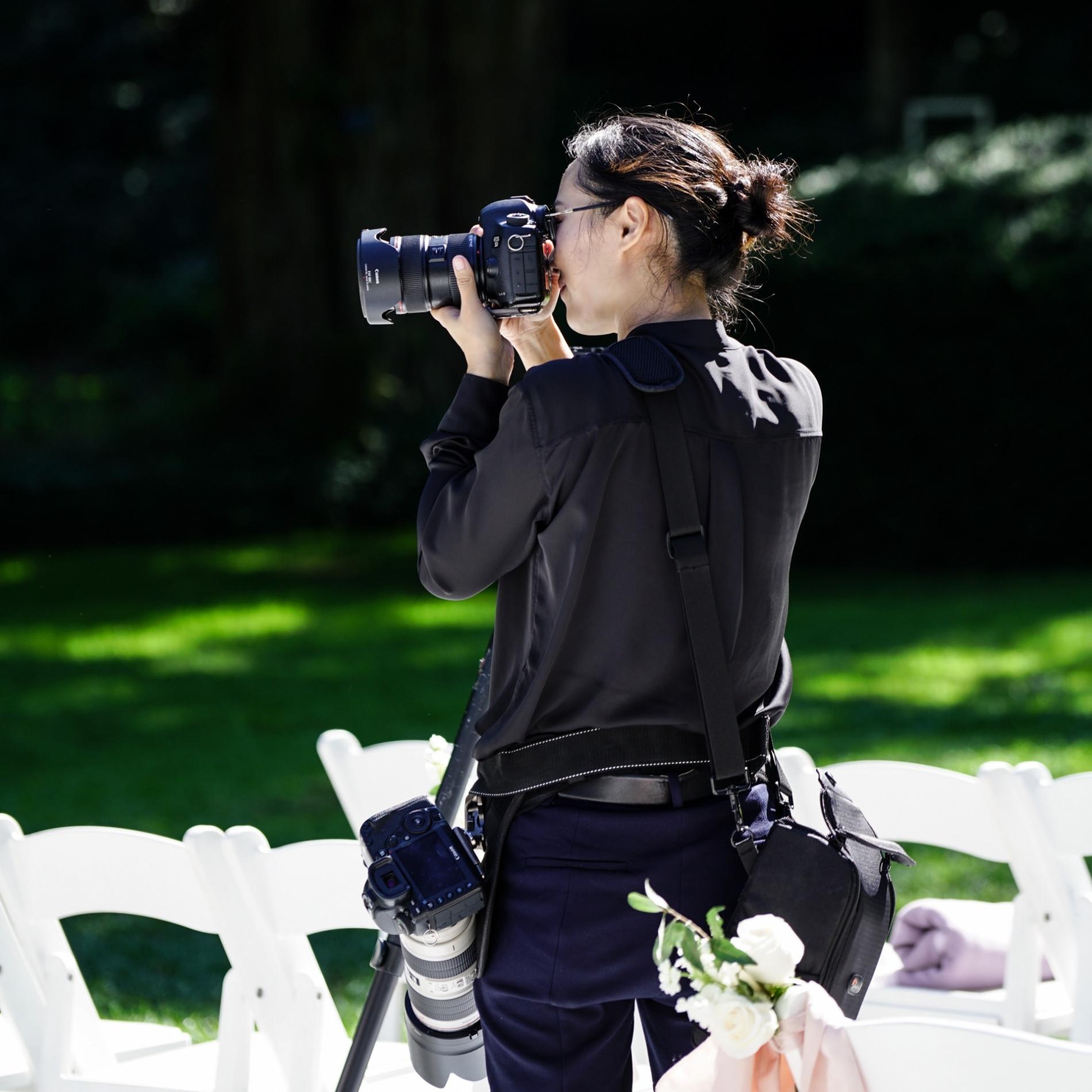Photographe de mariage Setauket New York avec appareil photo lors d'une cérémonie en plein air.