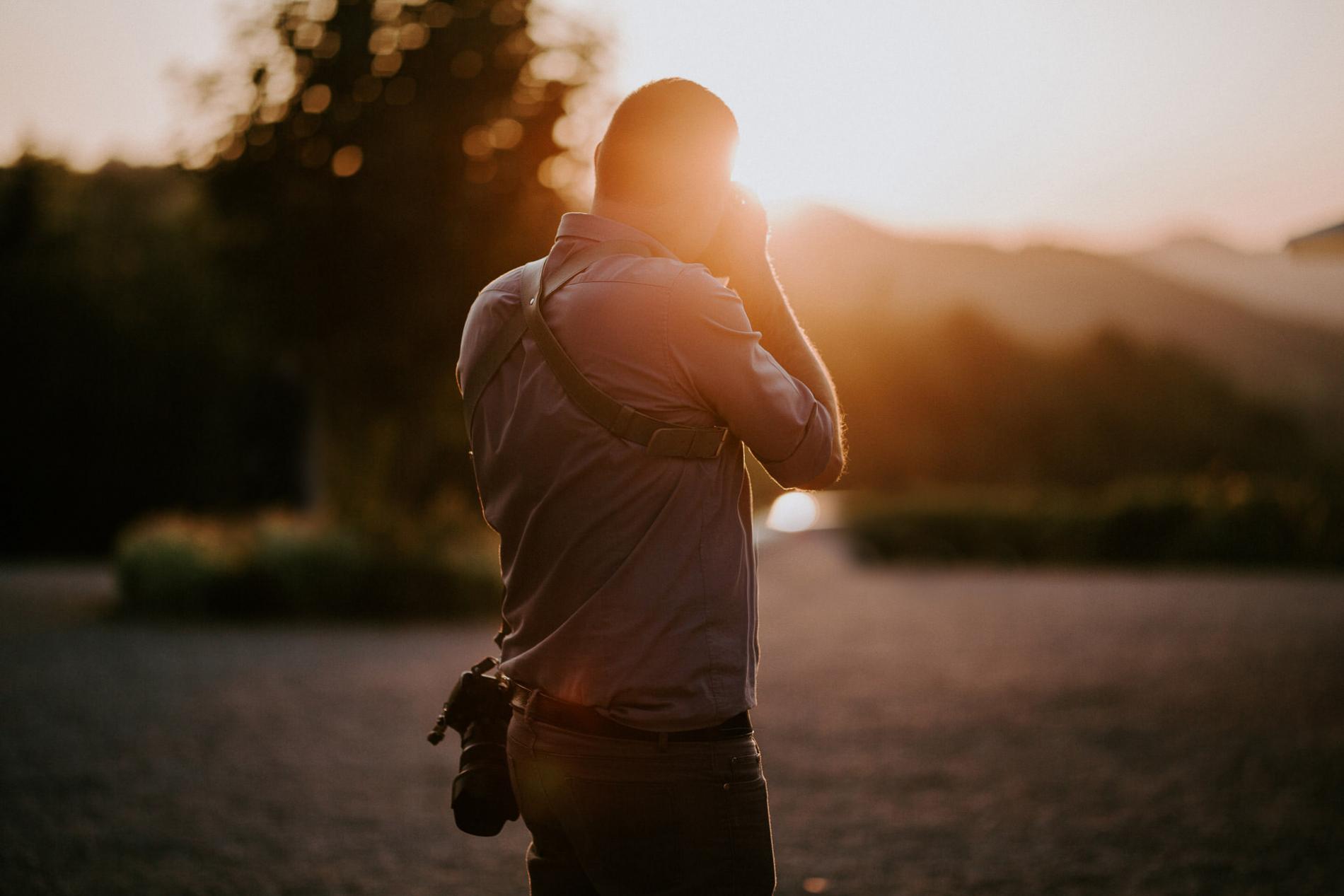 Verbania Verbano-Cusio-Ossola huwelijksfotograaf met camera bij zonsondergang.