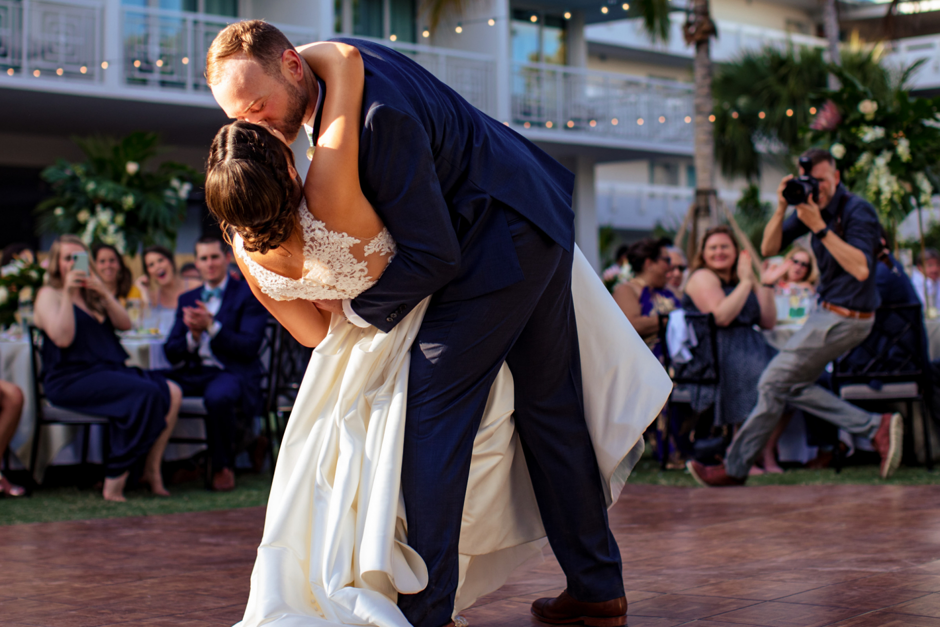 An Asheville North Carolina wedding photographer moves into place during a first dance dip kiss by the bride and groom