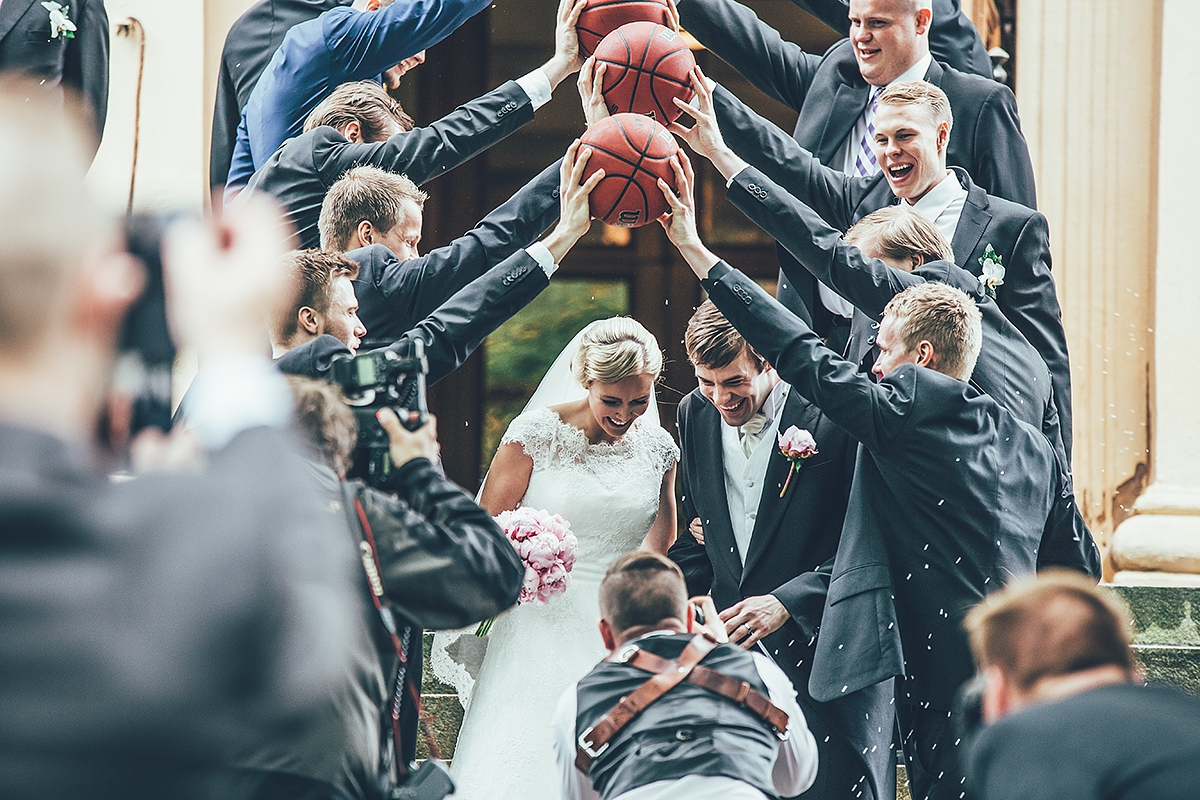 Veikkola wedding photographer working at an event with basketballs and the bride and groom.
