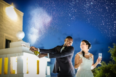 Monopoli wedding photographer captures the spray of champaign from the groom with his bride as his side
