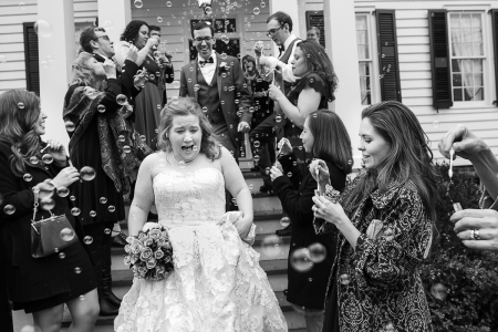 Bride and groom exit the Mary Gay House in a shower of bubbles