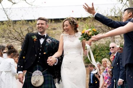婚礼摄影展示新娘和新郎与五彩纸屑被扔在希利·谷仓纽卡斯尔