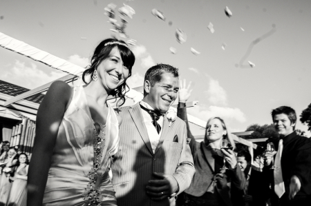 New Zealand black and white wedding ceremony celebration image of thrown flower petals over the bride and groom