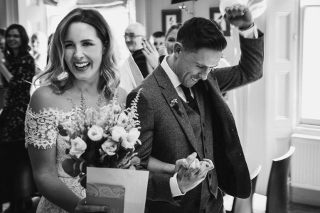Photo of the fist-pumping groom walking with the bride at The Rosendale, West Dulwich, London
