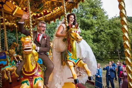 A noiva eo noivo montam cavalos de carrossel | fotografia de casamento no West Green House, Hampshire, Reino Unido