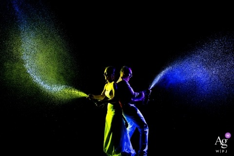 Chautauqua Dining Hall Wedding | Boulder Wedding Portraits of Bride and Groom Spraying Champagne at night with lights