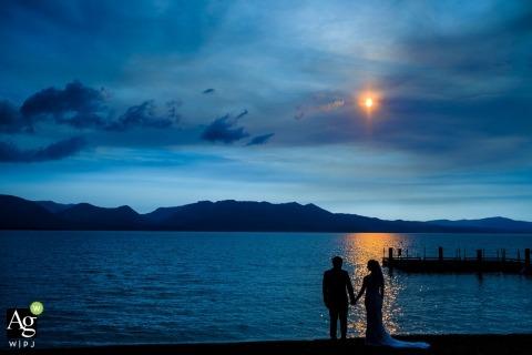 Fotografía de bodas en Lake Tahoe | La imagen contiene: silueta, novia, novio, lago, sol, montaña, vestido, tomados de la mano, retrato