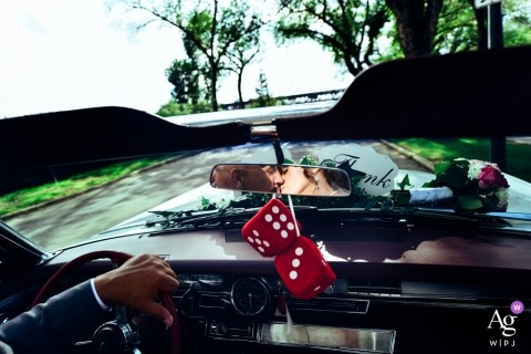Alberta Artistic Wedding Photograph of bride and groom in the rearview mirror of a convertible