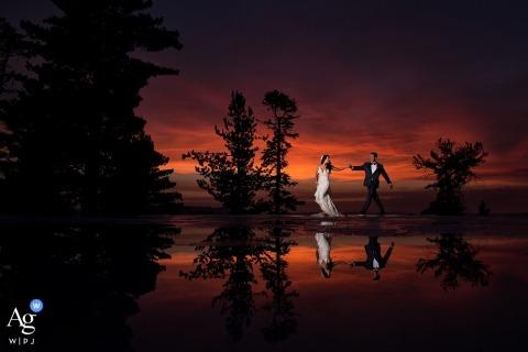 Fotografia artistica di nozze della California della sposa e dello sposo che camminano e riflessi al crepuscolo dagli alberi