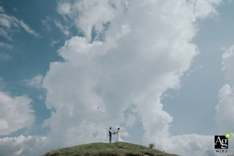 The clouds are bursting with the love of this wedding photo in Velenje.