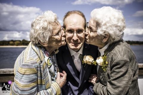 Noord Brabant Künstlerisches Hochzeitsfoto von zwei älteren Frauen, die einen Mann auf die Wangen küssen