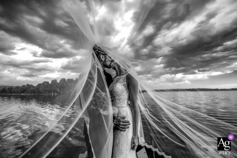 Lecco Artistic Wedding Photo | Bride and Groom under her veil outside with clouds in black and white