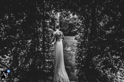 Lombardy bride walking with long dress train following in the garden