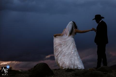Lo sposo del cowboy del Montana con la sua sposa del cowgirl fuori per un ritratto