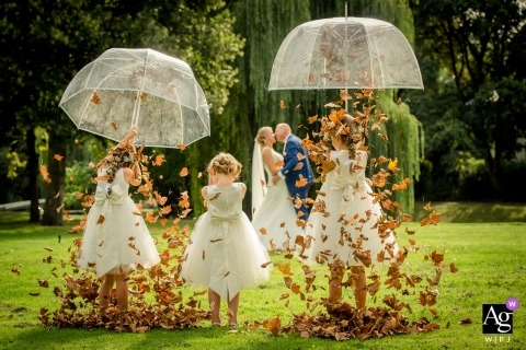 Netherlands flowergirls have it raining leaves from inside their umbrellas during portrait session with bride and groom