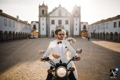 An outdoor wedding image of groom driving away with his bride on the back of his motorcycle in Portugal