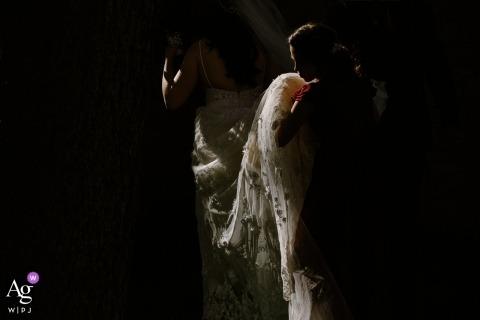 Fotografia di matrimonio creativa Missoula | dettaglio dello sposo con il treno del vestito da sposa della sposa