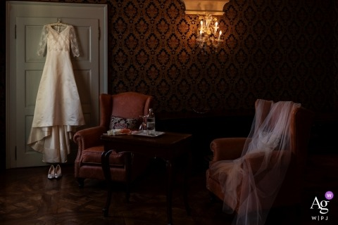 Tuscany creative wedding photography | detail of dress hanging on a door in room
