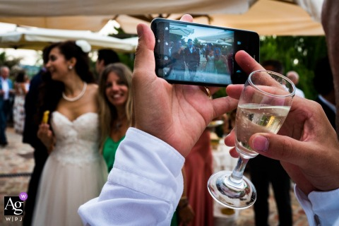 Fujian artistic creative photography detail of phone held by man, also holding champagne flute