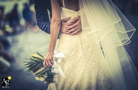La Spezia artistic creative photography detail of bride's bouquet with groom's hands around the waist of her dress