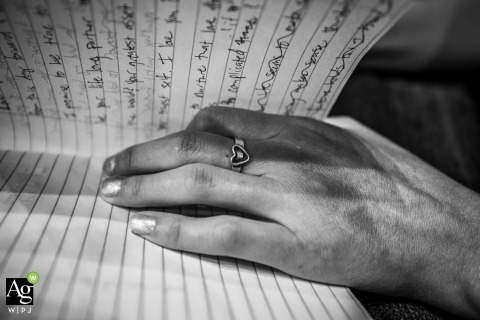 ring shot reading notebook with hand between pages - MN wedding photography