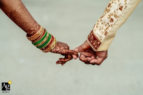 Canada artistic wedding photography details | bride and groom hands holding each other by their pinky fingers, bride with henna on arm and hand
