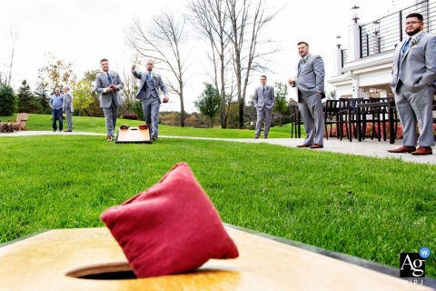 New Jersey wedding photography | detail shot of a bag hitting a corn hole board played by the groom and groomsmen