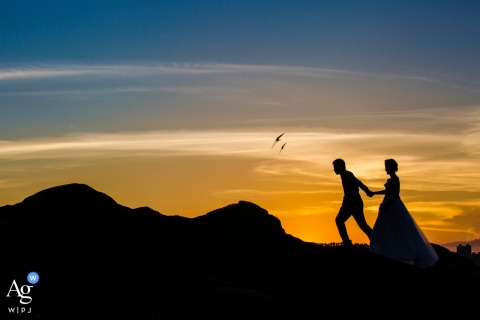 Longyan wedding day portrait of the couple silhouetted against the sunset, orange sky