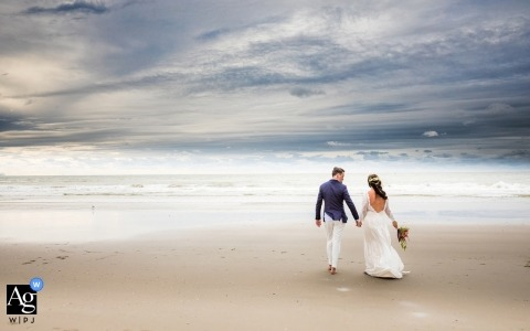 artistic wedding photo during Rotterdam portrait session with bride and groom on the beach at lowtide