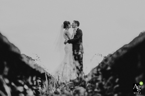 Creative and symmetrical portrait of a bride and groom centered in black-and-white from a low angle