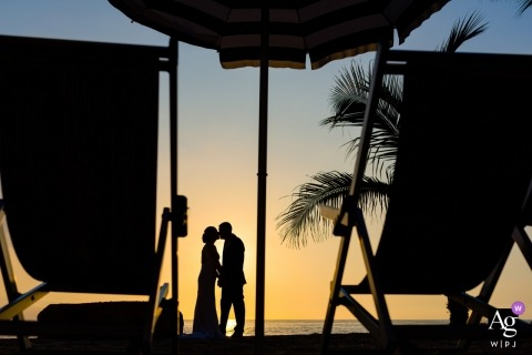 artistic wedding pictures of a Puerto Vallarta bride and groom on the beach with chairs, umbrella and palm tree