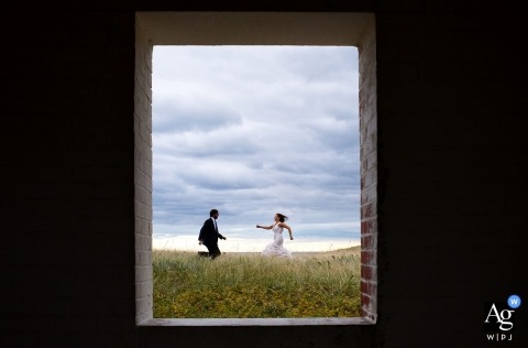 Nevada wedding day couple portrait | bride and groom running in the field, shot thorough open window