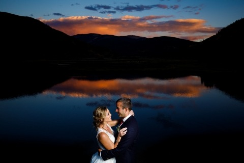 A sunset is reflected on the pond at Camp Hale as the couple poses during their fall wedding