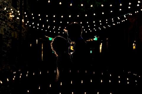Novia y novio sonríen el uno al otro bajo las luces del café