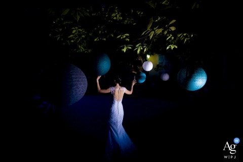 Lecco artistic creative photography detail of bride walking through hanging lanterns in trees at night