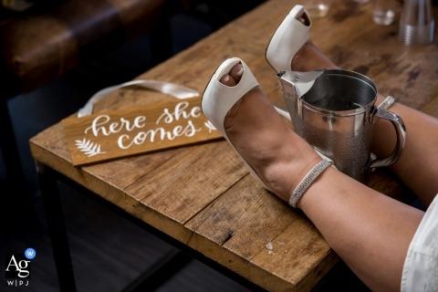 De fotografiedetail van de huwelijksontvangst van de schoenen van de bruid en een kop met een teken wordt geschoten dat | dekking voor Chicago, Ilinois bruiloften