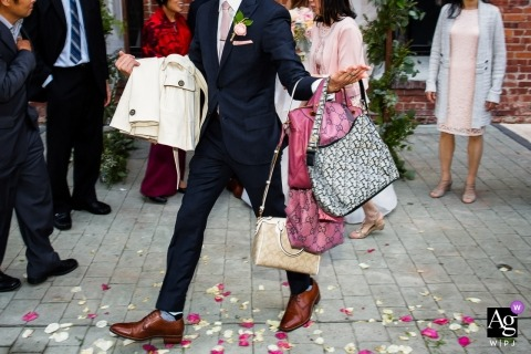 San Francisco, Ca destination wedding reception photograph of guy carrying purses and handbags | Argonaut Hotel, San Francisco wedding Details