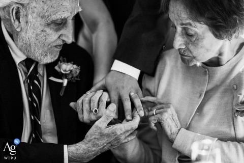 Photo de mariage de Saratoga Springs montrant des invités inspectant les bagues | capture des détails du mariage